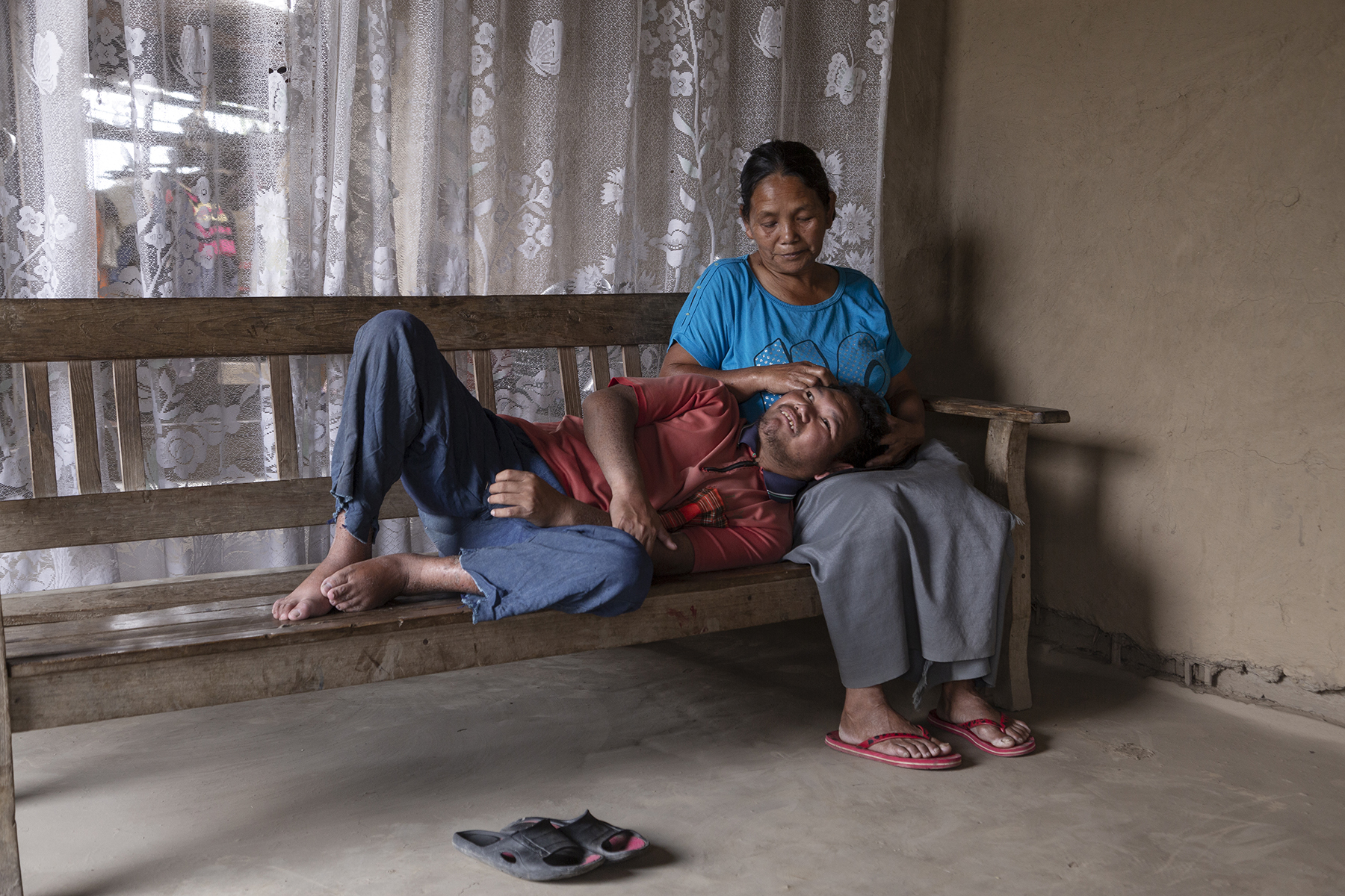 Sohkho wearing bluish grey pants and a faded red T-shirt is indoors, lying on a wooden bench with his head in his mother's lap. He is looking up at his mother Dimkhoneng who wears a sky-blue T-shirt and slate grey skirt. She is looking down at him and stroking his forehead with her right hand.