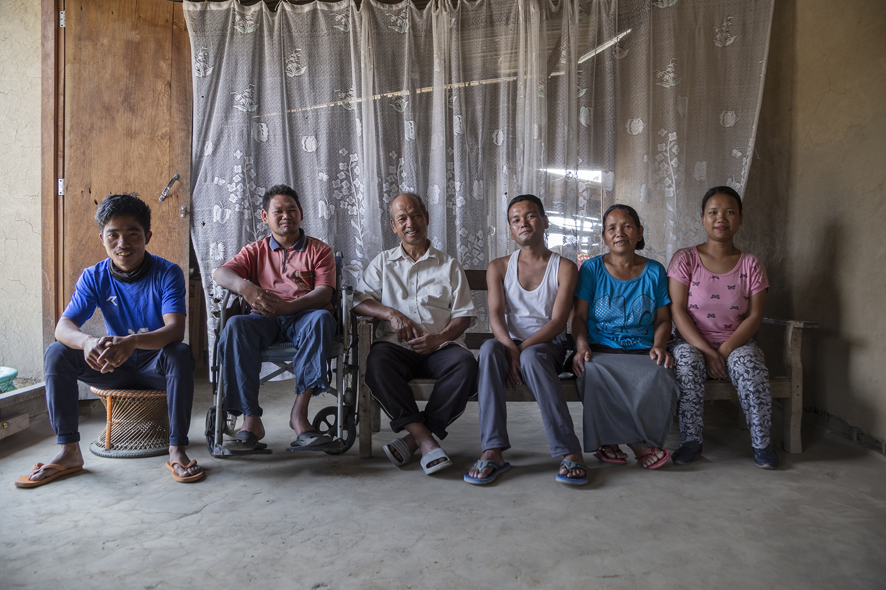 Sohkho poses with his family in a room with a mud floor and a transparent white curtain as the backdrop. From left to right: His sister's husband Lalminmang (29) wearing a royal blue T-shirt and navy blue pants sit on a bamboo cane moda (stool); Sohkho wearing a red T-shirt and bluish-grey pants sits in his wheelchair; next to him on a long wooden bench are his father Helkhothang (64) in cream half-sleeve shirt and brown pants; elder brother Solenmang (34) in sleeveless white banian (vest) and light grey pants; mother Dimkhoneng (64) in sky-blue T-shirt and grey skirt; and sister Ngaijahat (21) in pink T-shirt and grey pants.
