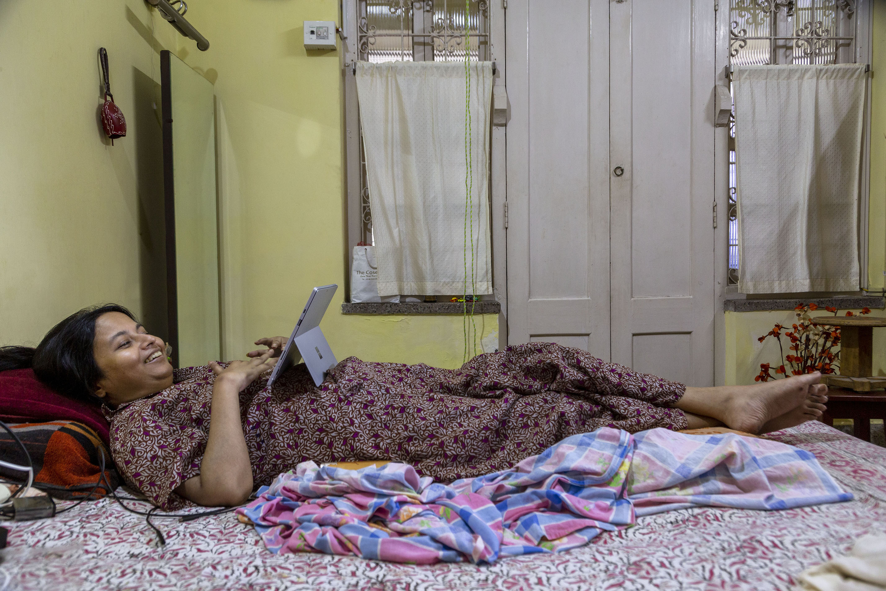 Soumita, wearing a gown in a maroon print, is lying flat on her back on her bed. Her hands rest on her chest and her legs are crossed at the ankles. She is smiling into an open laptop propped up on her stomach. The room has pista green walls. In the background is a door painted white. The door is between two windows with white curtains.