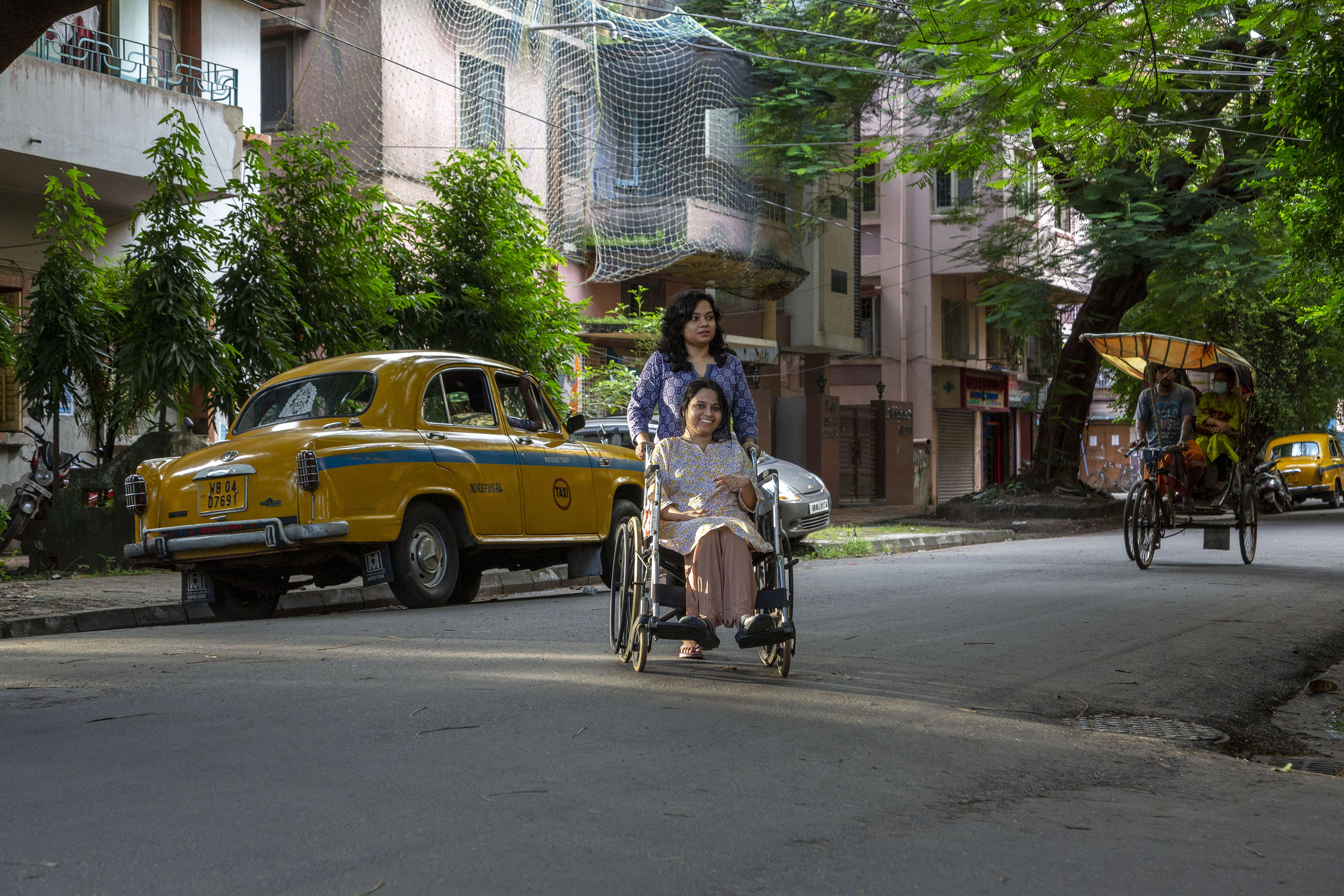 Soumita's younger sister Sayani is pushing her in her wheelchair and crossing a tarred road. A yellow Ambassador taxi is parked on the left side of the road. A cycle-rickshaw is coming towards us. The road is lined with trees and double-storeyed flats painted pink. Sayani, who has shoulder-length wavy hair, wears a full-sleeved kurta in a purple and grey print. Soumita is in a white kurta with a delicate yellow and purple print, and a peach-coloured salwar.