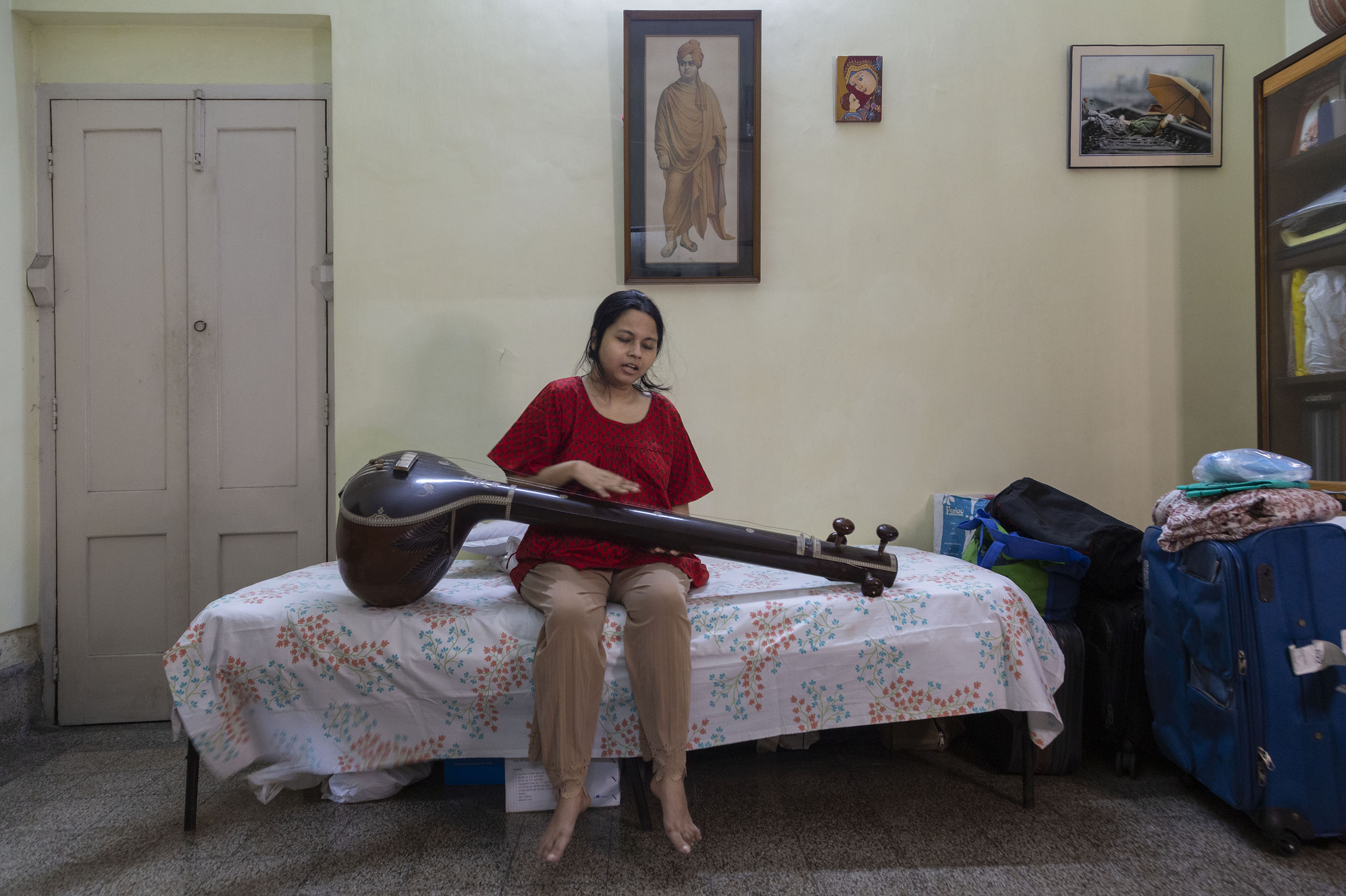 Soumita sits on a bed covered with a sheet printed with sprays of small blue and orange flowers. She wears a half-sleeved deep red top and peach-coloured salwar. Her bare feet are dangling. A dark brown veena is placed across her lap and rests on the bed. Her right hand hovers over the neck of the veena almost touching its strings. To the right of the bed is a huge dark blue suitcase placed upright on the floor, and to the left is a closed door painted white. On the pale green wall behind her hangs a framed full-length portrait of Swami Vivekananda in saffron robes.