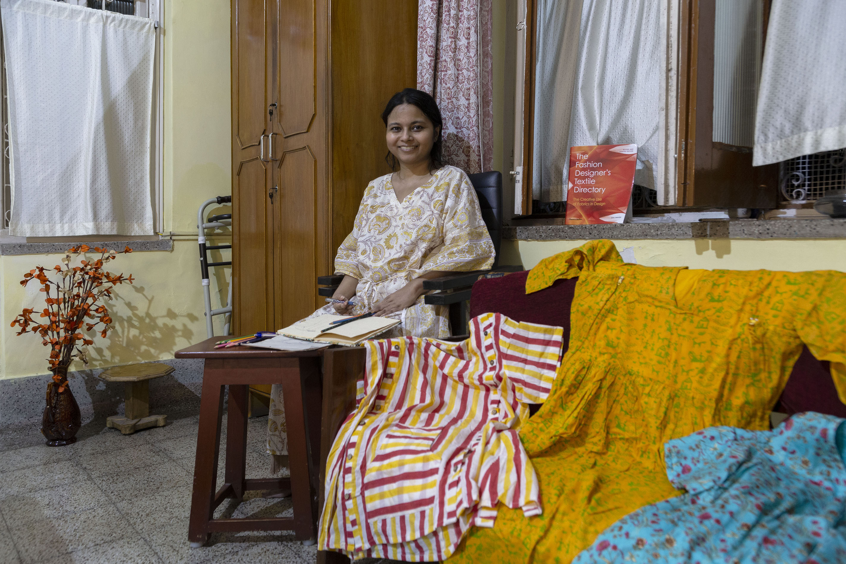 """Soumita Basu (39), wearing a loose gown in a yellow and brown print on a white background, sits on a padded chair in a room. She holds a pen in her right hand and an open notebook rests on her lap. There are colour pencils on a tall wooden stool in front of her. To the left is a wooden cupboard next to a window with a white curtain. To the right is a double sofa almost hidden by three large garments draped across it; they are adaptive clothes meant for those with physical disabilities. The gown on the left has vertical and horizontal panels of red, yellow and white candy stripes. The middle one is mustard yellow printed with small green images of tribal art. The gown on the right is sapphire blue with small pink flowers. A red book titled """"The Fashion Designer's Textile Directory"""" is propped up on the window sill behind the sofa. The window has white curtains."""