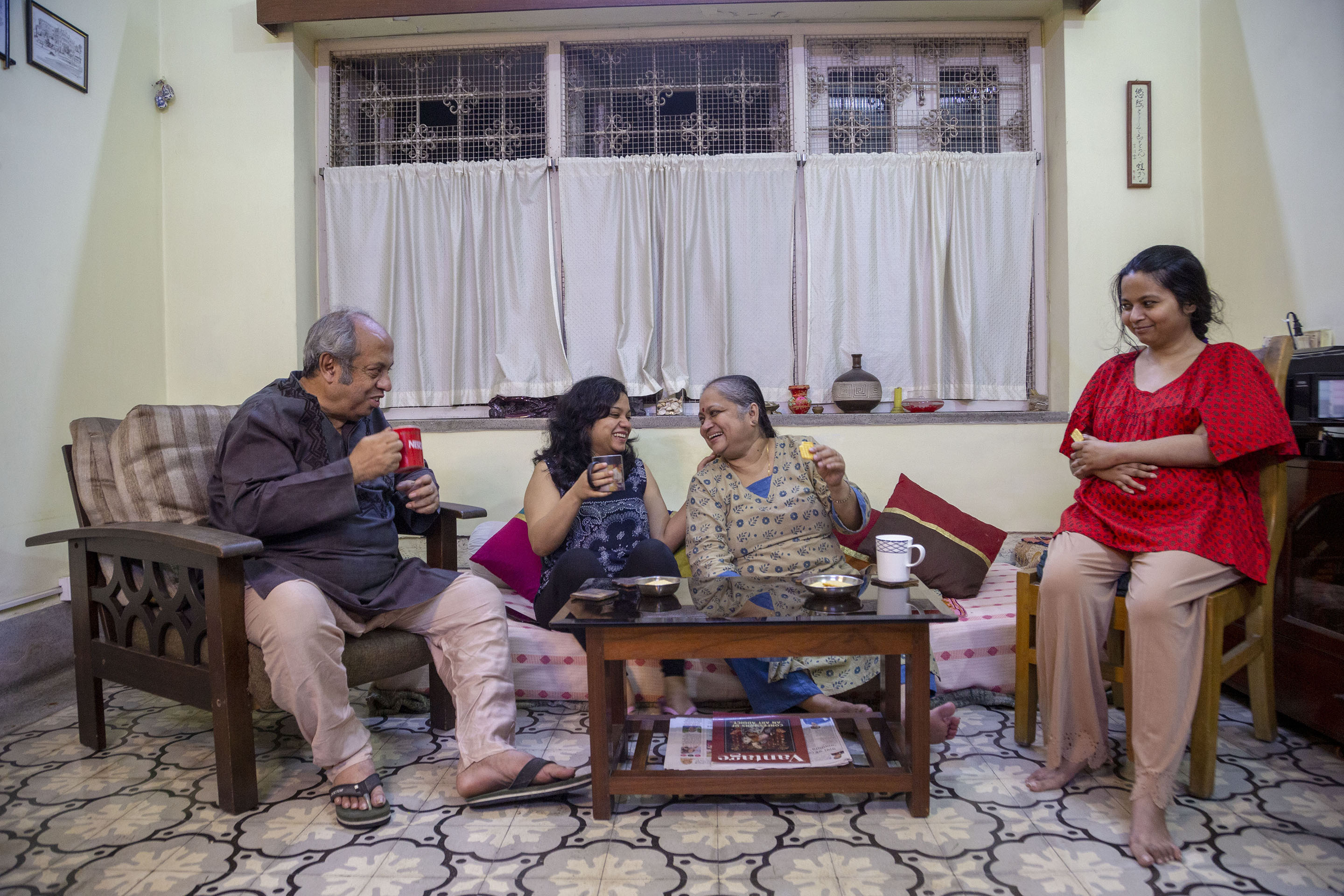 Soumita and her family, from left to right: father Amit Kumar Basu (68), sister Sayani Basu (34), mother Amita Roychowdhury Basu (60) and Soumita. Sayani and Amita are sitting on a divan while Amit sits on a wooden sofa and Soumita, in a wooden chair. There is a teapoy in the centre on which there are two steel plates of biscuits and a white mug. Amit, leaning against two fat rectangular cushions with light and dark brown stripes, holds a red mug. He wears a deep purple kurta and pinkish brown pyjamas. Sayani, holding a mug, is in a sleeveless deep blue kurta with sequins and embroidery on the front, and a deep blue churidar. Amita, in a beige and blue printed kameez and blue salwar, holds a cream-coloured biscuit. Soumita in a dark red top and peach-coloured salwar has folded her hands across her midriff. Amit and Soumita are looking towards Sayani and Amita who are looking at each other and laughing as if sharing a joke.