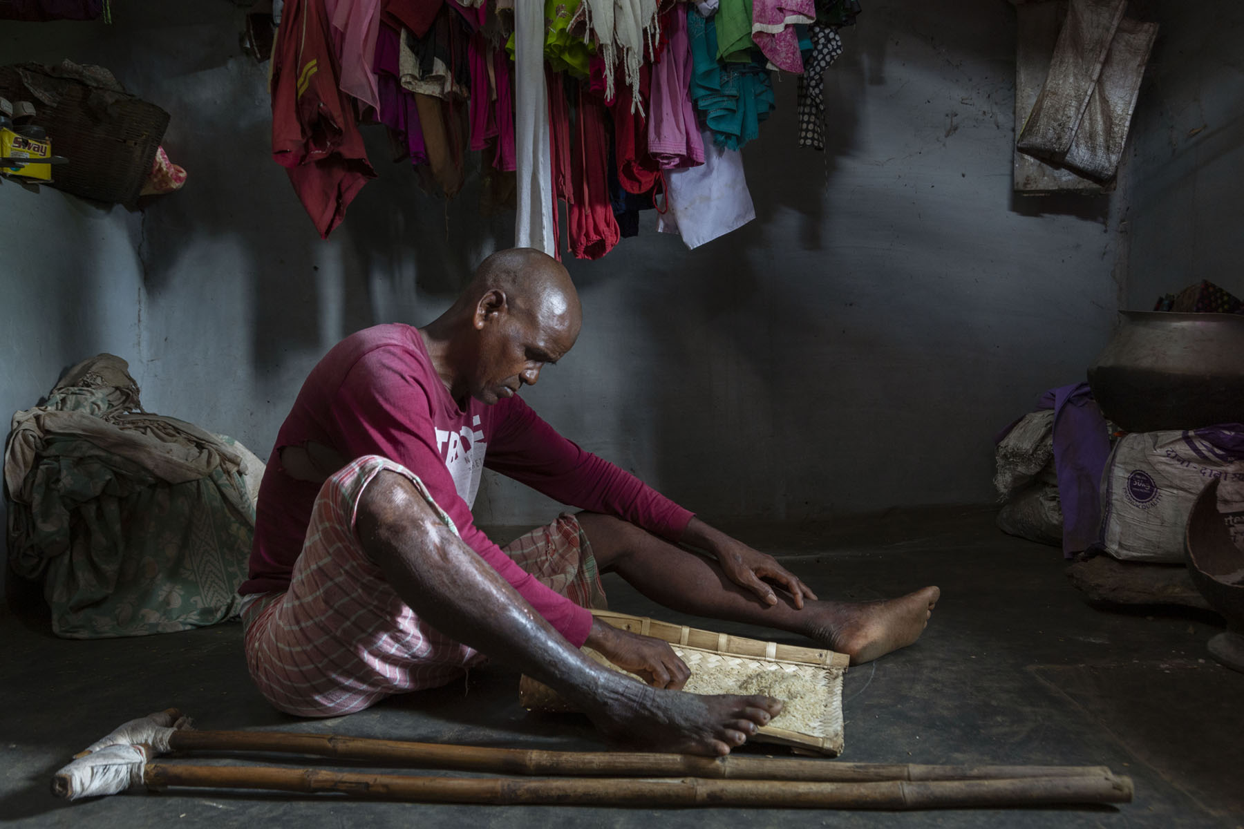 Suren wearing a maroon full-sleeved T-shirt and checked towel sits on the dark grey floor of a room with dark grey walls. His legs are stretched out and his crutches lie flat alongside him. Between his feet there is a woven bamboo tray filled with raw rice. He is looking down into the tray and picking out dirt from the rice. Just behind him, several dry clothes are hanging; there are men and women's clothes, mainly in shades of red and pink, bunched together.