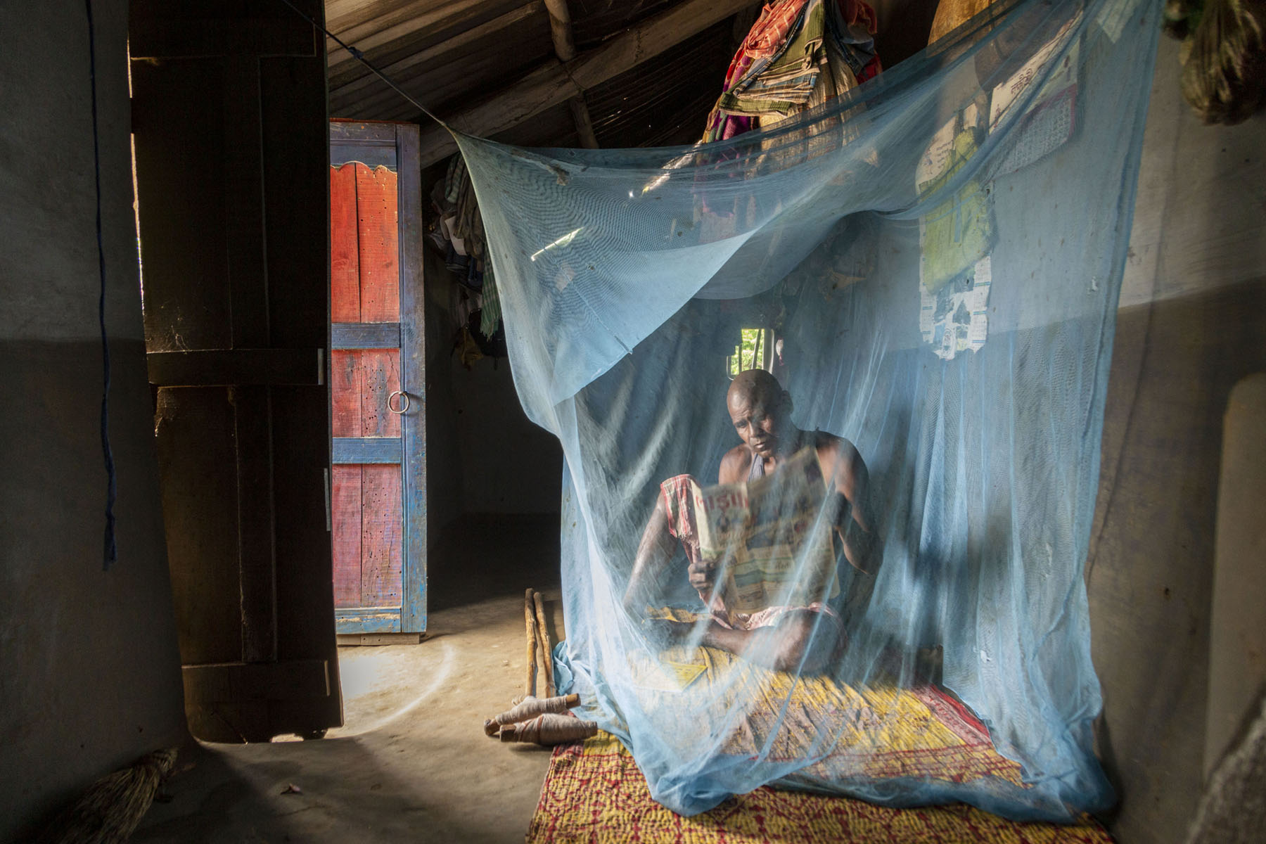 Sunlight comes into a room through an open wooden door painted red, and shines on Suren. He is sitting underneath a light blue mosquito net tied on top of a mattress on the floor. He is reading a Bengali newspaper that he is holding up with both hands.