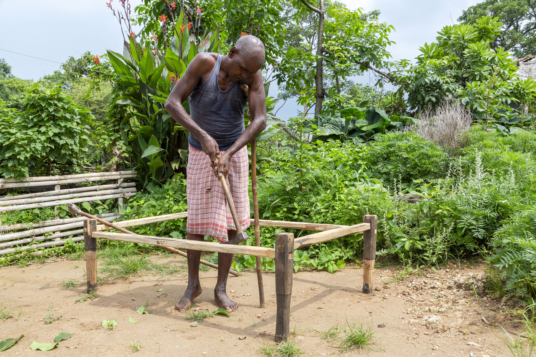 Suren is standing outdoors, inside the bare wooden frame of a cot that he is making. He is looking down, using both hands to grip the long wooden handle of a hammer. Behind him are trees and lush green plants including a canna with red flowers.