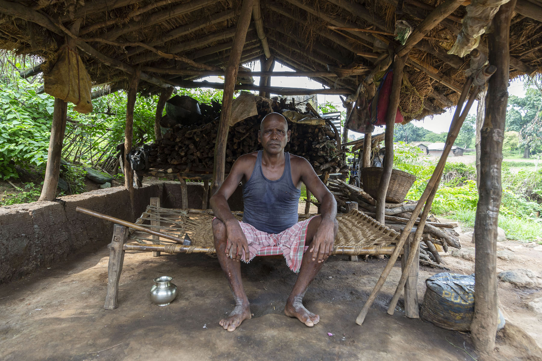 Suren Murmu (65) sits on a charpai (wooden string cot) in a small shed. He has a shaved head on which white stubble has grown. His hands are on his knees and he is looking straight into the camera. He wears a black banian and a faded red checked towel wrapped around his hips. The shed has a thatched roof propped up by wooden poles. It has no walls, the sides are open. Suren's wooden crutches are leaning against one of the upright poles. There is a small steel water pot on the floor next to his feet.