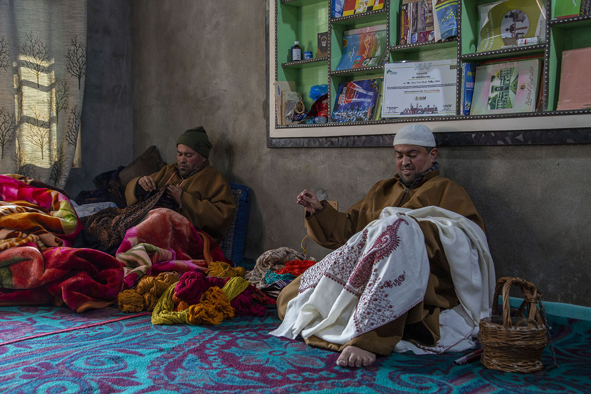 Tariq and his brother Farooq are sitting on a blue-and-pink carpeted floor, each holding a shawl on which they are doing sojni embroidery. Between them, several shawls of many colours are piled up.