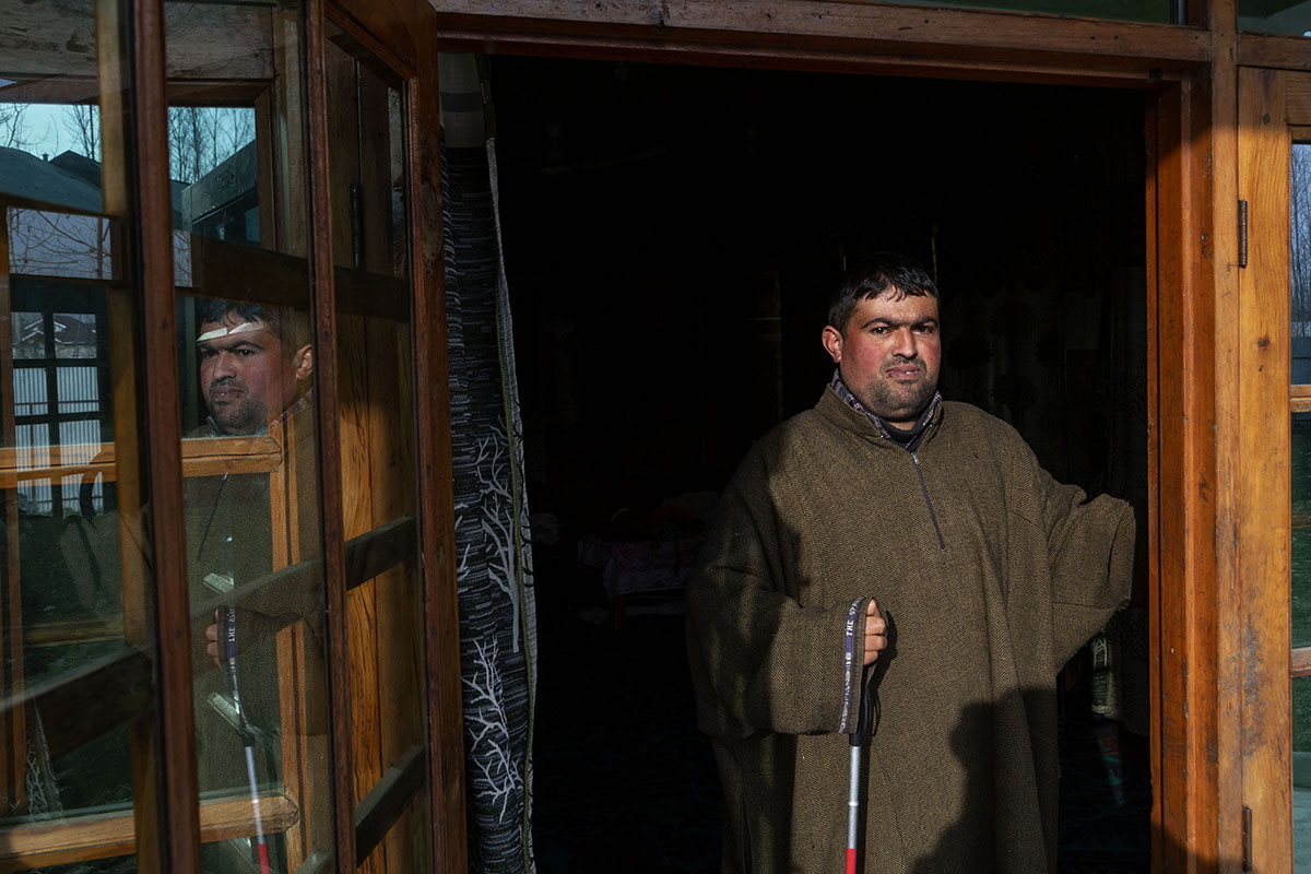 Tariq wearing a brown pheran and holding a cane is standing at an open door with sunshine falling across his body