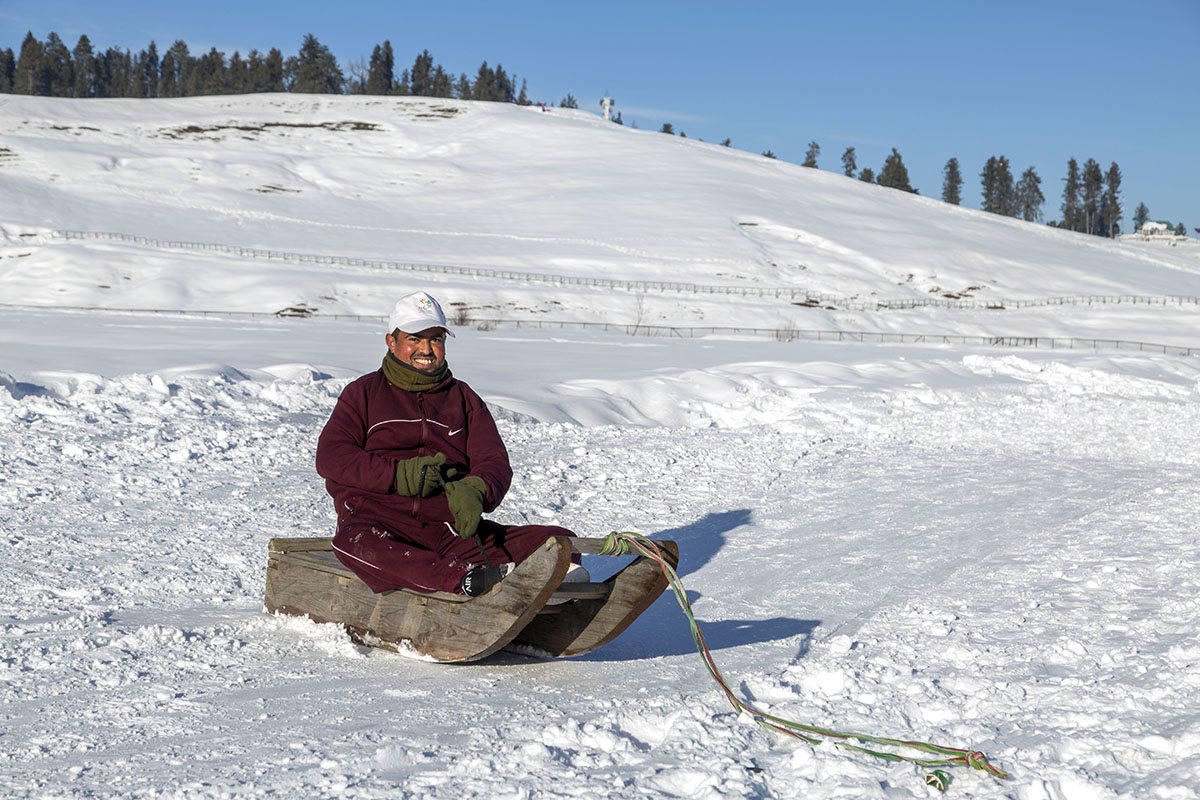 In the middle of a bare, snow-covered hill slope, a smiling Tariq Ahmad in a brown woollen pheran (long coat), muffler and white cap is sitting on a wooden sled