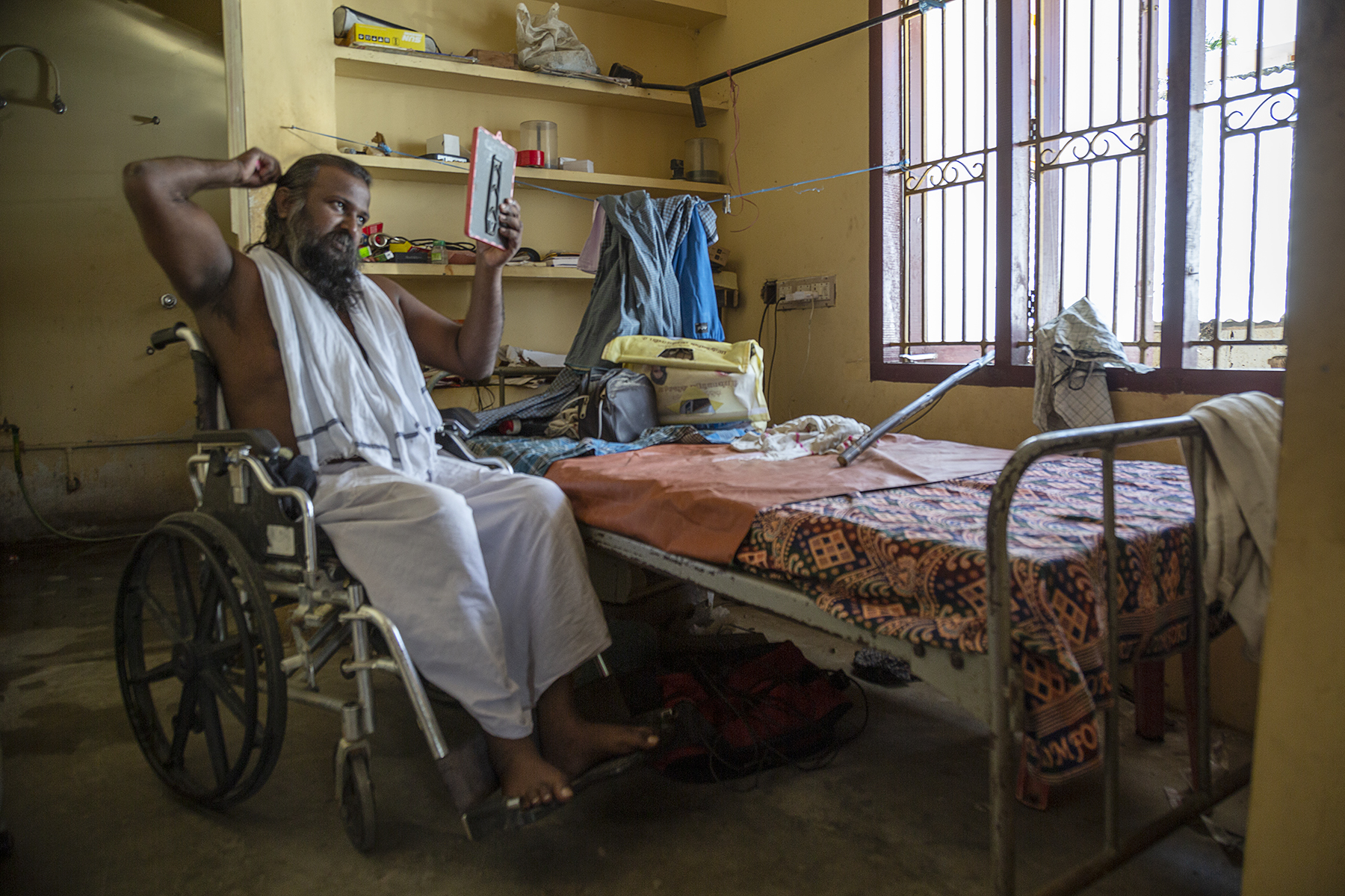Vallinayagam in white dhoti and white veshti sits in his wheelchair in his room. He is holding a mirror and combing his hair. Behind him are shelves built into the wall. To the right is a cot below a window with three panes. Two lungis and a pair of trousers bunched together hang on a clothesline strung between the wall and a window grill.