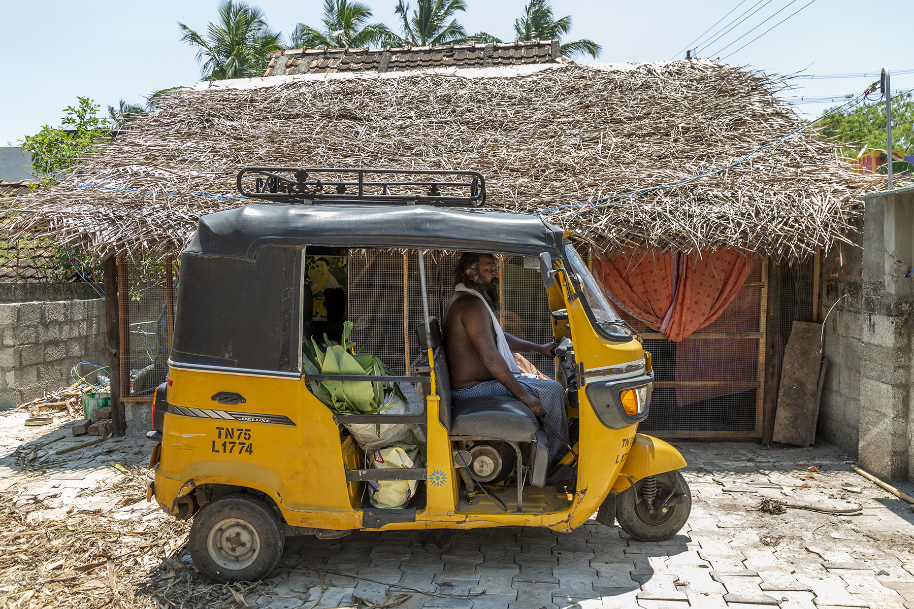 Side view of Vallinayagam sitting in his yellow autorickshaw parked in front of a small building which has a thatched roof of dry palm leaves. On the floor of the passenger seat is an upright bundle of plantain leaves.