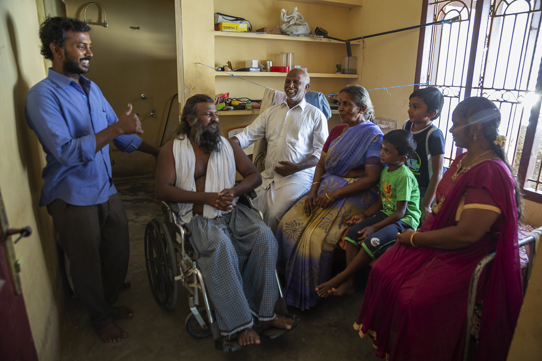 Vallinayagam in his room in his wheelchair is surrounded by his family. To the left of him stands his younger brother Mahesh (35), wearing long-sleeved blue shirt and brown pants, smiling broadly and giving a thumbs-up sign. The rest of the family is sitting on his bed to the right of him: his father Bhagavanar (63) who is laughing, in white shirt and white dhoti, mother Krishnammal (60) in blue and beige pattern sari, nephews Mukundan (6) and Balaji (9) in shorts and T-shirt, and sister-in-law Sakthi (31) in maroon salwar-kameez, who is smiling and looking at Vallinayagam.