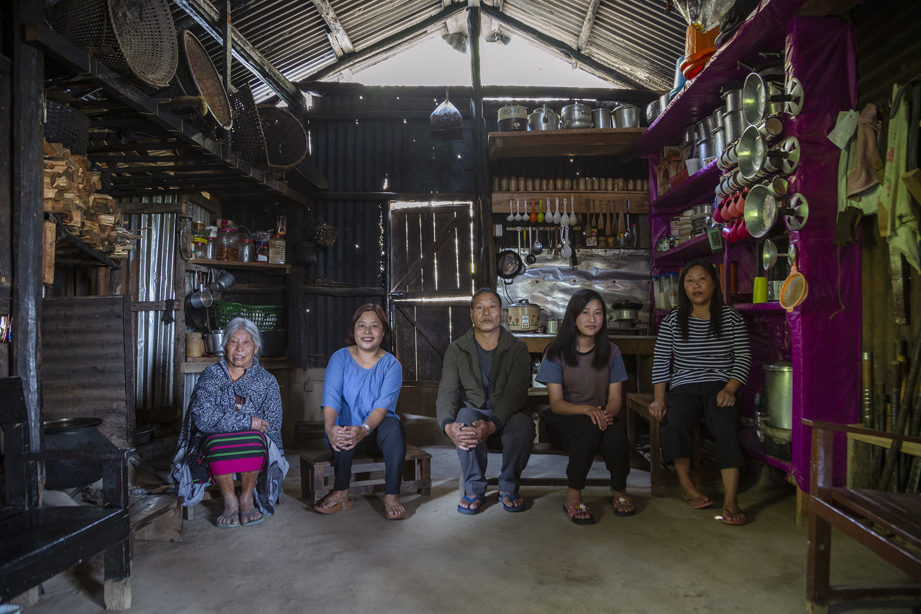 Vikengunu posing with her family seated on wooden benches in the kitchen area of a large room. From left to right: Her mother Hovineile Kera (84), with white hair tied back, wears a green, magenta and black striped Naga skirt with a large grey shawl wrapped around her arms and shoulders. Vikengunu (42) is in navy blue tight pants and sky-blue top. Her brother Vimeziho Kera (53) wears a brown jacket and grey trousers. Her niece Zavihonu Kera (16) wears a brown and grey round-necked T-shirt and black pants. Her sister Noekrunu Kera (43) wears black, knee-length shorts and a three-quarter-sleeve T-shirt with horizontal black and white stripes. They are surrounded by racks crammed with cooking utensils, and rows of hanging pans and spoons of different sizes.