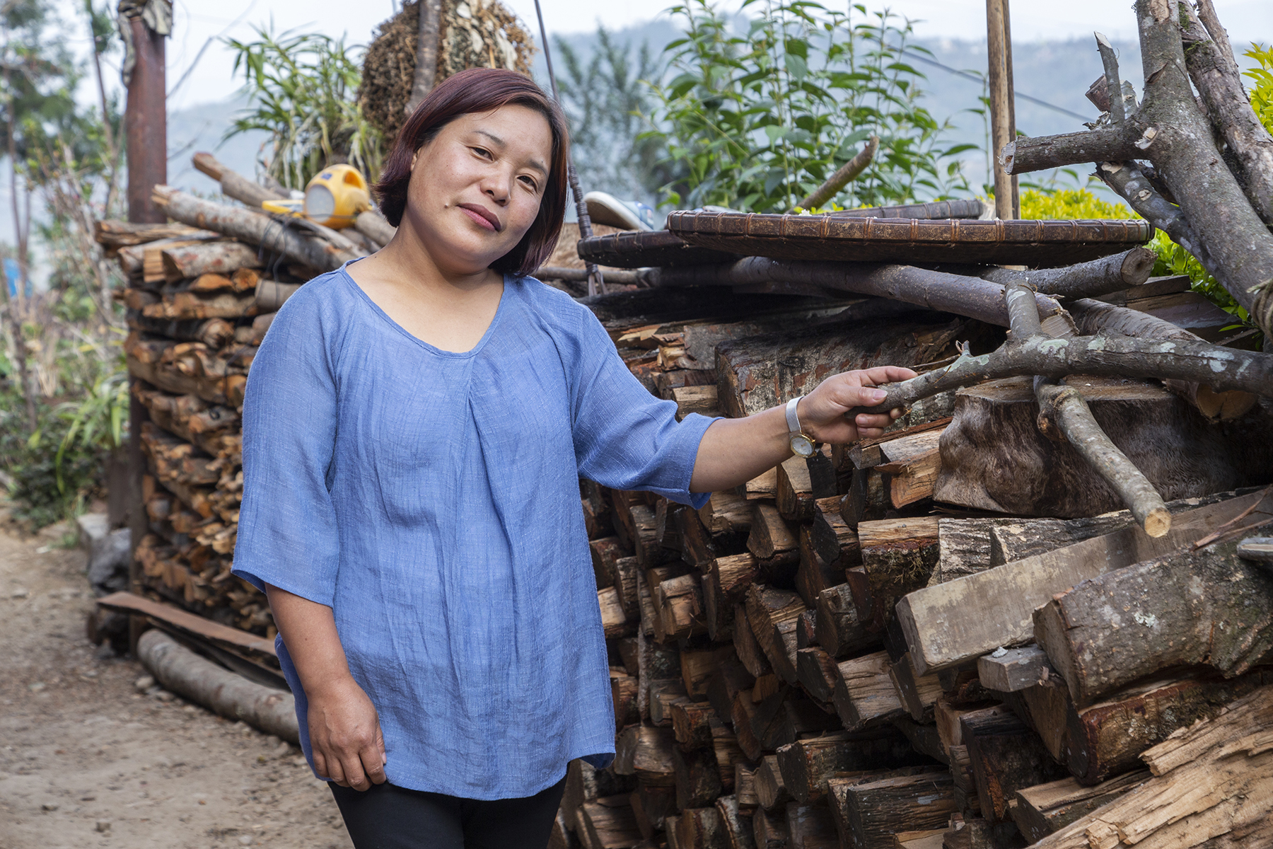 Vikengunu in a sky-blue top with three-quarter sleeves is standing outdoors next to a neatly arranged, shoulder-high pile of chopped branches used as firewood. Her neck is tilted slightly and she has raised one arm, wearing a watch with a silver strap, to touch one of the pieces of firewood.